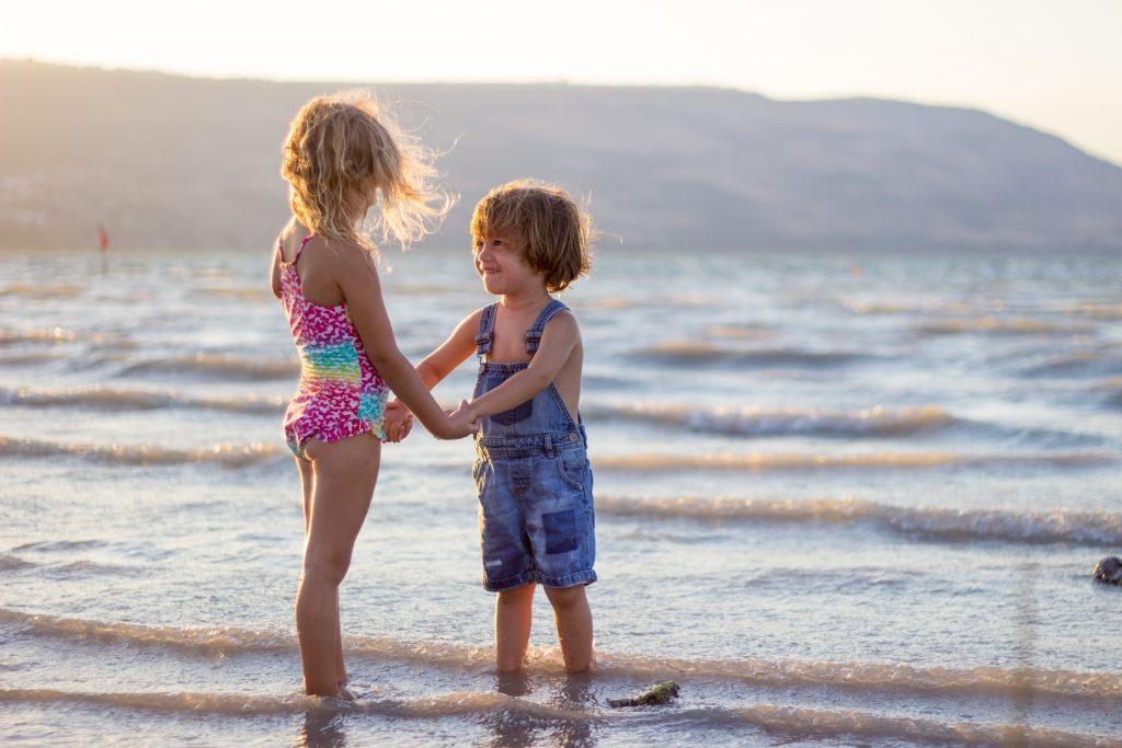 Young girl and boy enjoying the beach